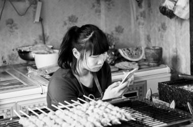 日本は技術、米国は軍事、欧州は観光、じゃあ中国は何で儲けてる?中国山東省青島市の旧市街地のレストランで、携帯を操作する従業員の女性(Gauthier DELECROIX)