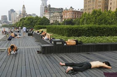 7月、猛暑が続く上海では、屋外で横になる人が続出。水辺に近い外灘 (バンド)の展望デッキで過ごす人々(目撃者撮影)