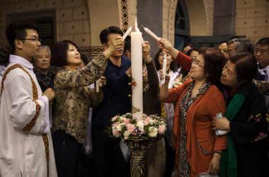 北京のカトリック教会で2017年4月、ろうそくに火を灯す教徒たち(Kevin Frayer/Getty Images)