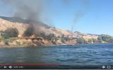 ジェットボートで水しぶきを飛ばし、消火を試みるカップル(スクリーンショット)