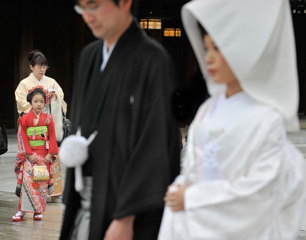 2008年11月、東京明治神宮で、伝統的な日本の結婚式を挙げる新郎新婦を見つめる女の子。七五三のお祝いで家族とお参りに来ている。(TORU YAMANAKA/AFP/Getty Images)