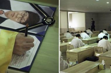 自分の棺桶の横で、遺書を書く参加者たち(NTD Inspired)