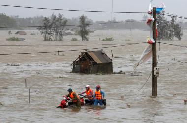 9月15日、台風19号(アジア名:トクスリ)が、ベトナム中部を直撃し、住宅損壊、停電、洪水などの被害をもたらしている。トクスリの勢力はベトナムに上陸する台風としては過去数年で最大。洪水の中バイクを押す人たち。ハティン省で撮影(2017年 ロイター/Nguyen Huy Kham)