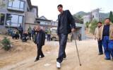 村人と歩く鮑喜順さん。身長の高さが一目瞭然だ。(FREDERIC J. BROWN/AFP/Getty Images)