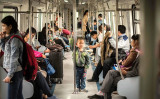 2016年4月、北京の中心地を走る電車の中、手すりにつかまる少年(FRED DUFOUR/AFP/Getty Images)