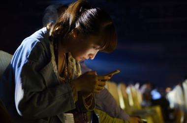 2017年4月、北京で、スマートフォンのオンライン会議に参加しているため、画面に見入る若い女性。注:記事中の失明した女性ではない(GREG BAKER/AFP/Getty Images)
