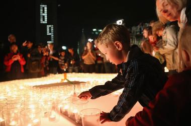 共産党政権を崩壊させた抗議活動の記念行事でロウソクを灯す男の子。2014年、ドイツ・ライプツィヒで撮影。(Photo by Sean Gallup/Getty Images)
