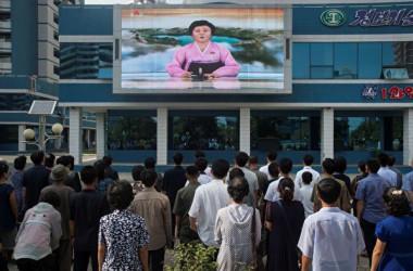 北朝鮮の首都平壌で、スクリーンで放送される国営放送を見つめる北朝鮮の市民(KIM WON-JIN/AFP/Getty Images)