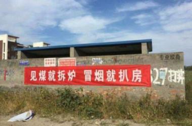 中国当局は大気汚染対策として、集中暖房供給システムを石炭から天然ガスへの切り替えを進んでいる。写真は、町で掲げられているスローガンだ。「石炭を見かけたらボイラーをすぐに壊そう。煙をみたら家を取り壊そう」と書かれている。(ネット写真)