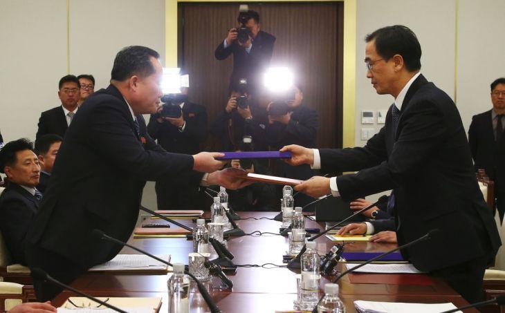9日、握手をかわす韓国の趙明均統一相(右)と北朝鮮の李善権・祖国平和統一委員会委員長(左)(AFP/Getty Images)