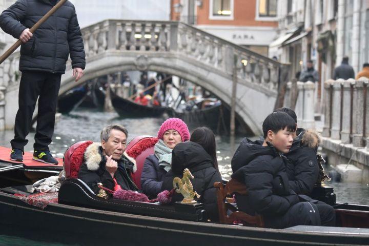 イタリア著名な観光都市ベネチアで、市を流れる河を船で渡る外国人観光客。2018年1月19日撮影、参考写真(ANDREA PATTARO/AFP/Getty Images)