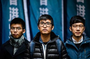 香港終審法院は6日、2014年大規模な民主化運動「雨傘運動」を主導した元学生団体リーダーの3人に対して、2審での実刑判決を取り消し、16年8月の1審判決を維持する判決と言い渡した。写真は黄之鋒氏(左)、羅冠聡氏(中)と周永康氏(右)。(ANTHONY WALLACE/AFP/Getty Images)