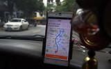 中国配車アプリ大手の滴滴出行はこのほど、ソフトバンクと合弁会社を設立し日本市場参入の計画を発表した。写真は2016年5月13日、中国のタクシー運転手が広西省桂林市の街で運行中に滴滴出行のGPS機能を使っている場面。(GREG BAKER/AFP/Getty Images)
