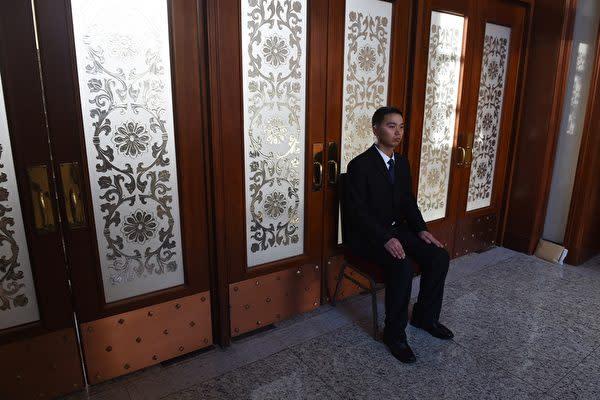 中国全国人民代表大会の報道官は4日、国家主席任期撤廃についてコメントを行った。写真は16年3月7日北京・人民大会堂にいる警備スタッフ。(GREG BAKER/AFP/Getty Images)