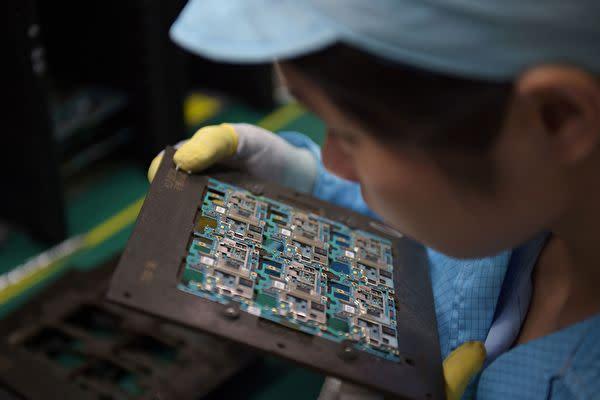 中国李克強首相が5日の全人代会議で、当局主導の製造業振興策「メイド・イン・チャイナ2025計画」をあらためて強調した。写真は、広東省東莞市にある携帯電話用半導体メーカーの労働者。(NICOLAS ASFOURI/AFP/Getty Images)