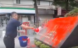 3月7日午後、日本の台湾窓口事務局「日本台湾交流協会」の玄関近くにある石碑に、中華統一促進党の幹部の男が赤いペンキをかける様子。まもなく逮捕された(スクリーンショット)