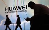 スペイン/バルセロナにある中国ITメーカー華為(HUAWEI、ファーウェイ)のロゴ前でスマートフォンを操作する男性 、2016年2月撮影(Lluis Gene/AFP/Getty Images)