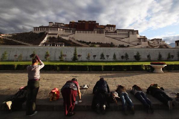 五体投地してポタラ宮を礼拝する人々 (Photo by Feng Li/Getty Images)
