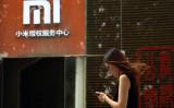 2015年8月15日、北京の小米サービスセンター前を通る女性 (Greg Baker/AFP/Getty Images)