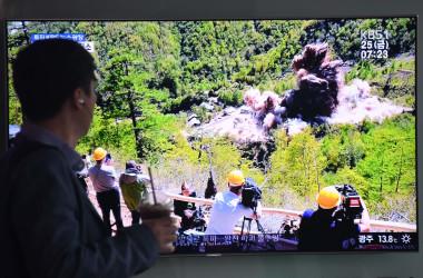 24日、北朝鮮は北東部プンゲリ(豊渓里)にある国内唯一の核実験場で坑道を爆破したと発表した。写真は爆破の様子を伝えるテレビ画面を見る韓国の市民(JUNG YEON-JE/AFP/Getty Images)