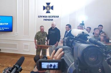 ウクライナ保安局の記者会見に姿を見せたジャーナリストのアルカディ氏(中央の黒いパーカの男性)警察は前日に同氏が「射殺された」と発表していたため、本人の登場は周囲を驚かせた Twitter@polina__ivanova)
