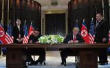 6月12日、初の米朝首脳会談を終え、合意文書に署名するトランプ米大統領と金正恩朝鮮労働党委員長(SAUL LOEB/AFP/Getty Images)
