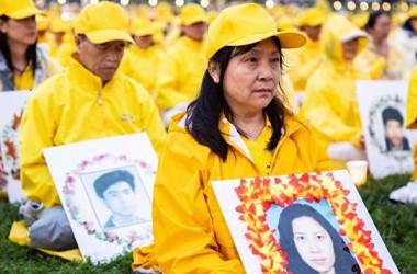 今年6月22日、世界各地から集まった法輪功愛好者約1万人が米首都ワシントンDCで開催された集会で、当局の弾圧で死亡した妹の遺影を抱く女性学習者(Samira Bouaou/大紀元)