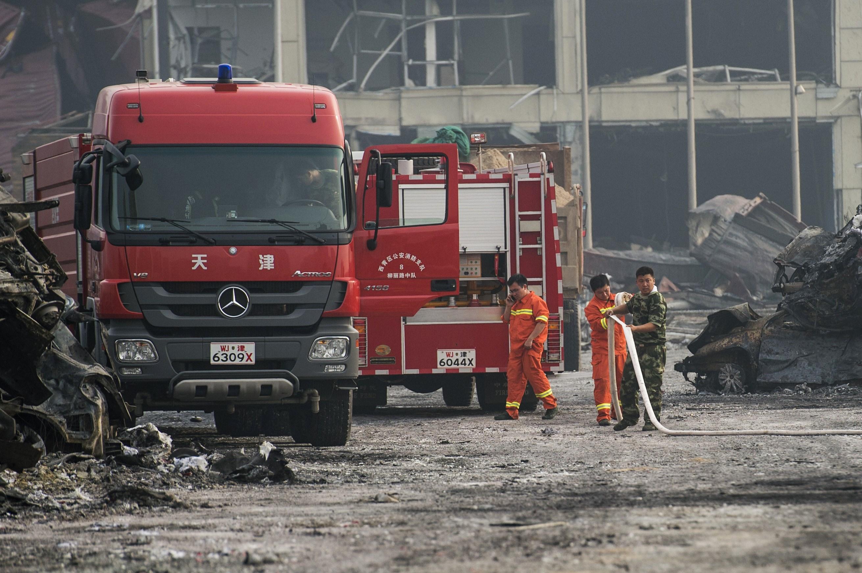 天津爆発事故の現場で、消火活動にあたる消防隊員と兵士(FRED DUFOUR/AFP/Getty Images)