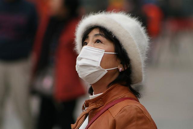 マスクを着用し、北京の灰色の空を見上げる中年女性。参考写真 ( theglobalpanorama/Flickr)