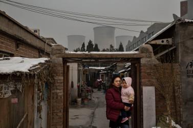 北京郊外の古い街で赤ん坊を抱く女性、石炭コークス炉が遠くに見える。11月27日撮影。中国政府は2030年までの早い時期に、二酸化炭素(CO2)排出量をピークにさせ、以後は減少させるとしている。11月30日~12月11日、フランスのパリで国連気候変動会議(COP21)が開催され、地球温暖化防止の策として、参加国はCO2排出量枠を主要議題にする予定。(Kevin Frayer/Getty Images)