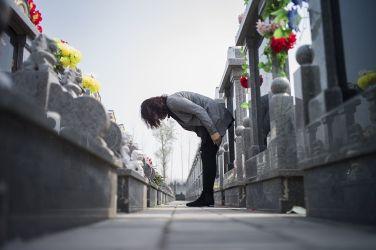 上海は墓の価格が住宅の4倍と高騰。写真は墓石に一礼する女性(FRED DUFOUR/AFP/Getty Images)