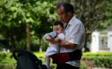 専門家によると、少子化問題が中国の社会と経済の発展の歯止めとなり、人口問題は中国最大の危機だという。写真は、赤ん坊を世話する高齢者(WANG ZHAO/AFP/Getty Images)