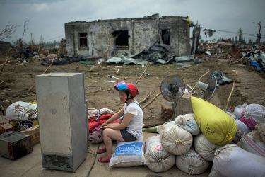 中国江蘇省塩城市阜寧県で28日、竜巻で破壊された家屋のそばに座る女性。23日に起きた竜巻と嵐により99人が死亡、800人以上がケガを負った。(JOHANNES EISELE/AFP/Getty Images)