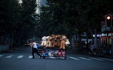 2016年7月、上海市内でぬいぐるみ製品を運ぶ労働者。中国では最近の税制改革をうけて、複雑な税制に注目が集まり、怒りの声があがる(JOHANNES EISELE/AFP/Getty Images)