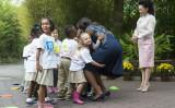 ワシントンのスミソニアン国立動物園で、子供たちとハグするミシェル・オバマ米大統領夫人と、傍らでほほ笑む彭麗媛・習近平主席夫人。2015年9月の習主席訪米期間に訪れた(MOLLY RILEY/AFP/Getty Images)