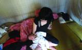 小学校6年生の女子児童は、2013年5月に女の赤ちゃんを出産した。写真は、赤ちゃんをあやす、強姦被害に遭ったとされる少女(南都ネット/スクリーンショット)