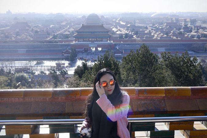 2016年12月22日、北京の紫禁城を背景に立つ女性。最新の研究では、北京のスモッグには、抗生物質への耐性を持つバクテリアが含まれているという(WANG ZHAO/AFP/Getty Images)