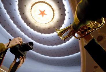 2016年3月14日、北京の人民大会堂で開かれた中国共産党第十一届中央委員会第三次全体会議の閉幕式で、演奏するブラスバンドを撮影するカメラマン (WANG ZHAO/AFP/Getty Images)