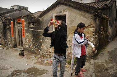 2012年3月、中国広東省の烏坎(ウーカン)村で、お菓子を口にする女の子たち(PETER PARKS/AFP/Getty Images)