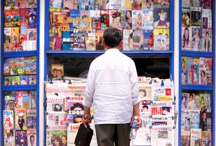 北京で2000年5月、ニューススタンドの前に立つ男性(STEPHEN SHAVER/AFP/Getty Images)