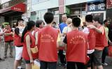 2013年8月、在米中国人の多い米ニューヨーク市フラッシング地区で、共産党主導の反カルト運動のゼッケンを着てアンチ法輪功のビラを撒いていた中国系の若年者たち。大紀元記者を囲み話している(大紀元)