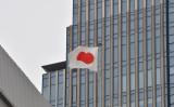 内閣府は18日、1~3月期のGDPは年率2.2%と発表した。東京のビル屋上にはためく日の丸の国旗(KAZUHIRO NOGI/AFP/Getty Images)