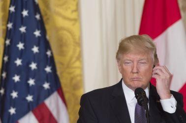 トランプ大統領の型破りな「電話外交戦略」とは?2017年2月、カナダのトルドー首相と共同記者会見で、イヤホンを調整する米トランプ大統領(SAUL LOEB/AFP/Getty Images)