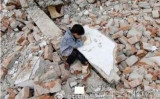 取り壊された自宅のがれきの上で宿題をする子供(インターネット)