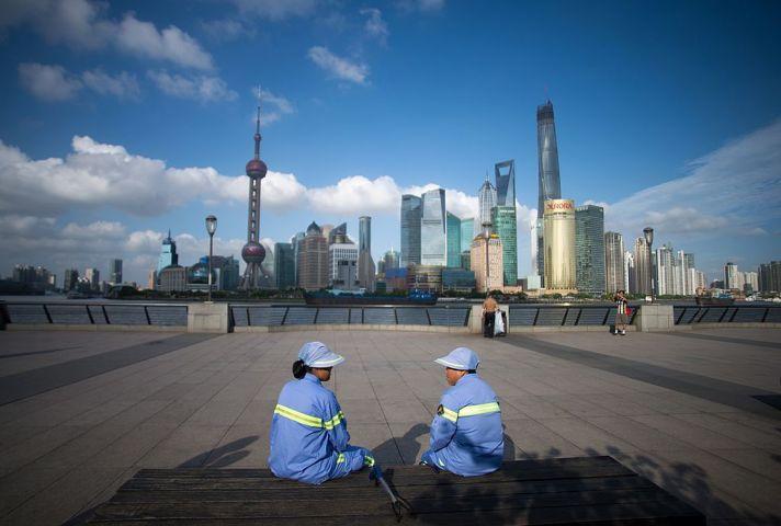 人権弁護士は大紀元の取材に対して「中国の民衆が目覚めつつある」と語った。上海タワー近くで休憩する清掃作業員たち(JOHANNES EISELE/AFP/Getty Images)