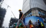 7月、北京の建設現場近くを歩く作業員(WANG ZHAO/AFP/Getty Images)