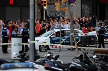 テロの発生したバルセロナ中心街で、手を挙げて警察の調べを受ける人々(JOSEP LAGO/AFP/Getty Images)