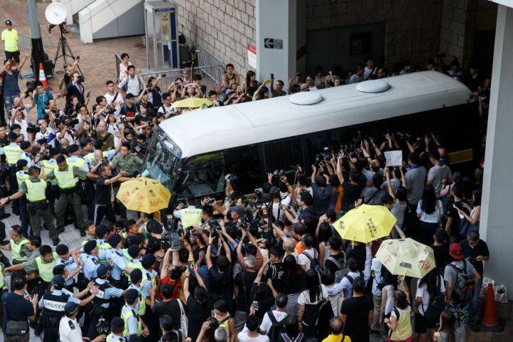 香港民主化運動「雨傘革命」で筆頭に立っていた若者3人が、17日、最高裁判所に護送される様子。報道陣、警官、支持者らでごった返す(STR/AFP/Getty Images)