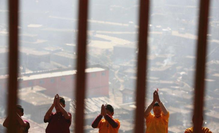四川省カンゼ・チベット族自治州にある仏教学校で合掌する若い仏僧(China Photos/Getty Images)