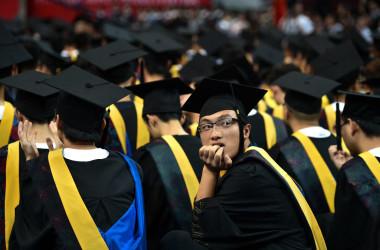 若者たちを狙ったねずみ講が中国で横行している。6月20日、武漢にある華中科技大学の卒業式で振り返る卒業生。参考写真( STR/AFP/Getty Images)